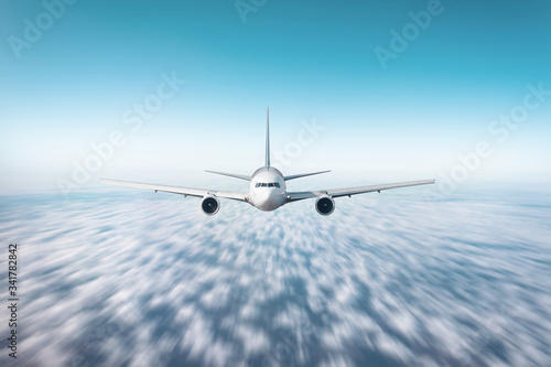 Wide-body airplane flies over cumulus clouds with speed effect, exactly front view Fototapet