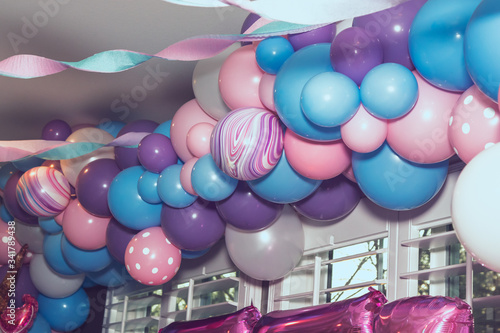 Photo A view of an artsy pastel colored balloon design attached to the ceiling, in a home living room setting