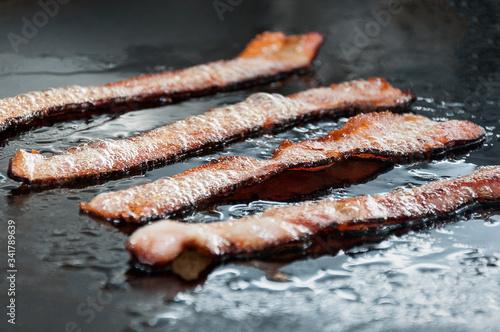 Fototapeta bacon strips being fried on a snack plate obraz