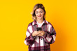 canvas print picture - Young Russian woman isolated on yellow background sending a message with the mobile
