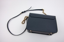 Blue Crossbody Bag With A Metal Gold Handle On A White Background. The Rich Blue Color In Combination With Gold.