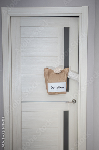 Photo a gloved courier gives a donation bag without personal contact during a pandemic