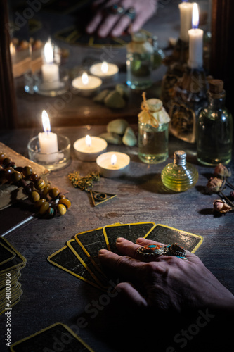 Fotografering Hands of a sybil with fortunetelling cards and burning candles is reflected in a