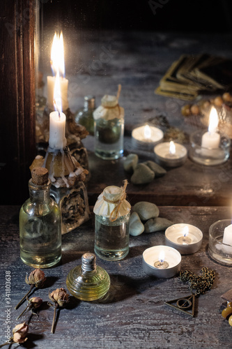 Burning candles, fortune-telling cards and tincture bottles are reflected in an Fotobehang