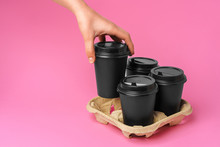 Coffee Delivery. Human Hand Holding Takeaway Coffee Cup On Paper Background