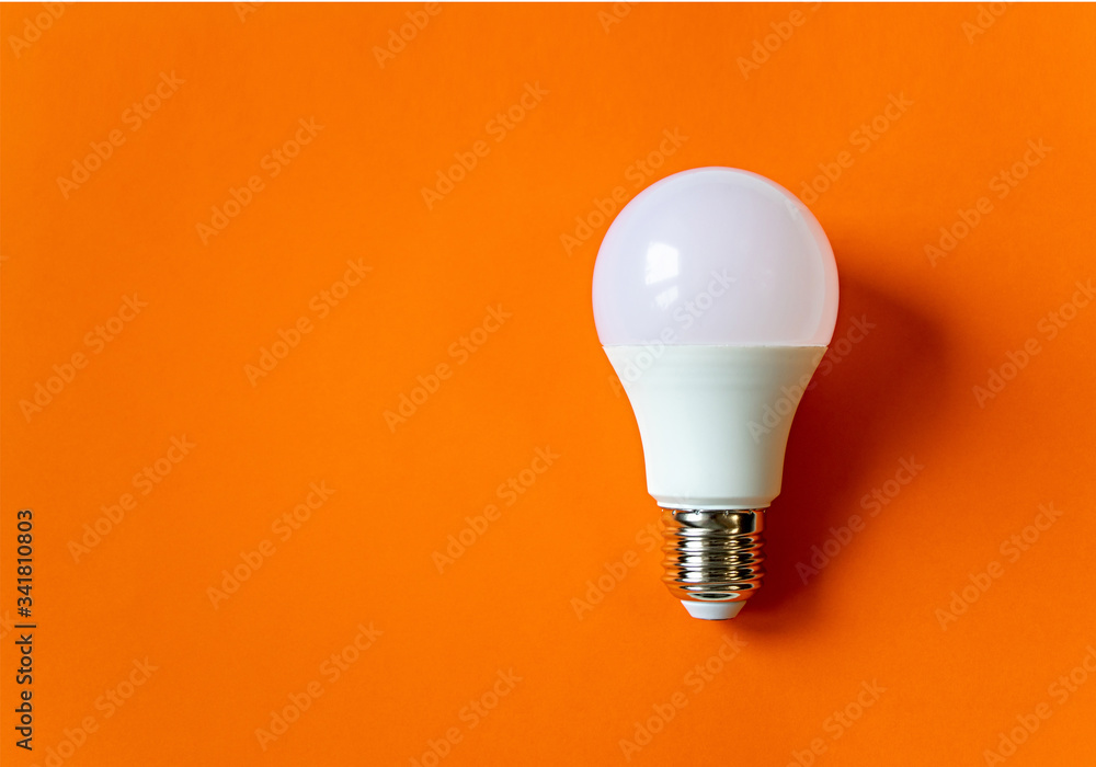 Fototapeta White energy saving light bulb on an orange background with copy space. LED white bulb, concept of new idea