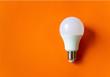 Leinwanddruck Bild - White energy saving light bulb on an orange background with copy space. LED white bulb, concept of new idea