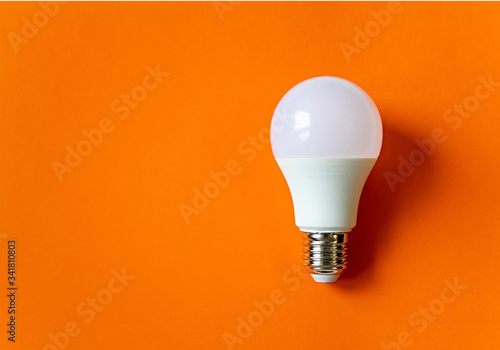 Obraz White energy saving light bulb on an orange background with copy space. LED white bulb, concept of new idea - fototapety do salonu