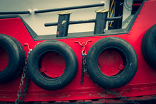 Old Car Tires On Board A Ship. Rubber Wheels Protect The Boat From Impact. Steel Lining Of The Side Of The Tugboat.
