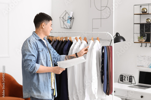 Male Asian stylist near rack with clothes in studio Fototapet