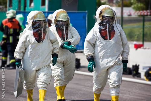 Obraz Three men in protective gear disinfecting contaminated areas or cleaning up after chemical or radiation accident. The inflatable gear protects against contamination with viruses, radioactive particles - fototapety do salonu