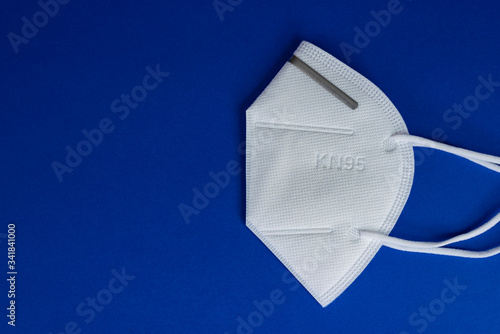 Obraz KN95 or N95 white mask with antiviral medical mask for protection against coronavirus on blue background. - fototapety do salonu