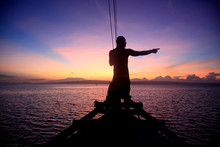 A Young Man Sitting On The Deck Of A Sailboat At Sunrise, The Man Is Pointing His Finger Towards The Horizon. Komodo National Park. Indonesia