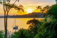 Sailboat Anchored During A Sunset In The Tranquil Dolphin Bay, Panama