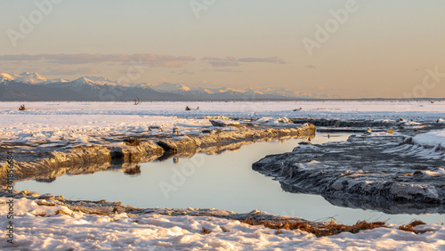 Photo Tidal channel winding through snow covered area with mountains in the background at sunset