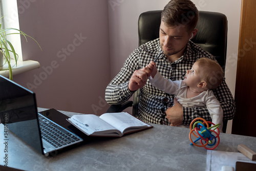 Photo Young father working from home office and babysitting his happy smiled baby girl