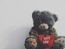 Teddy Bear With Red Heart Shape Against White Background