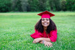 canvas print picture - Portrait of a beautiful multiethnic woman in her graduation cap and gown. Smiling and cheerful as she poses lying down in the grass