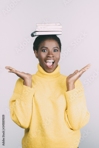 Amazed beautiful African American woman with books on head Wallpaper Mural