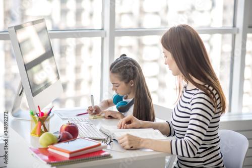 Dark-haired girl and her tutor sitting at the table doing homework Fototapet
