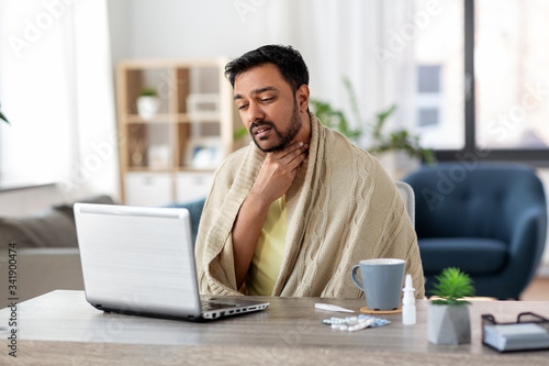 healthcare, technology and people concept - sick indian man in blanket with sore Fototapete