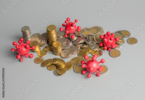 Photo Coronavirus outbreak in 2019,Flu COVID-19 virus cell with coins money on a gray background,Covid-19 Affecting the global economy concept