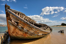 Abandoned Boat Moored At Beach Against Sky On Sunny Day