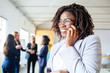 Closeup shot of smiling businesswoman talking on smartphone. African American young woman with dreadlocks looking at distance. Communication concept