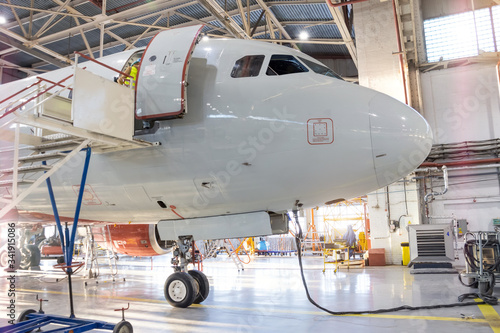 Front nose of the aircraft cockpit and front landing gear in the avia hangar for maintenance Canvas Print