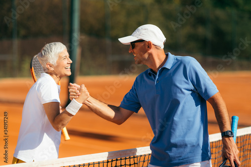 Photo Tennis Instructor with Senior Woman in her 60s Handshaking after Having a Tennis Lesson on Clay Court