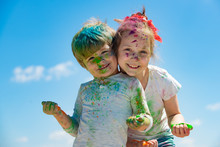 Portrait Of Bright Kids Smeared In Colored Powder Holi. Bright And Funny Little Children Playing With Colors Of Holi.