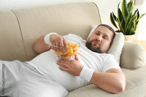 Photo Lazy overweight man eating chips on sofa at home