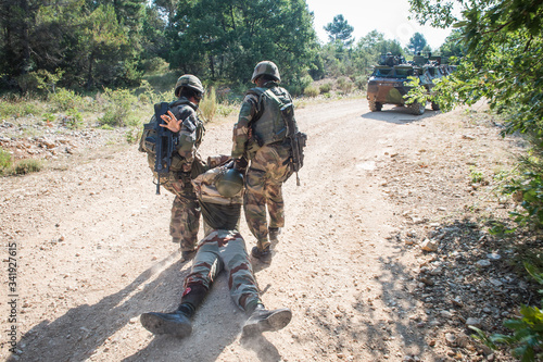 Fotografía Soldiers rescuing a fake wounded man during simulated conflict between soldiers