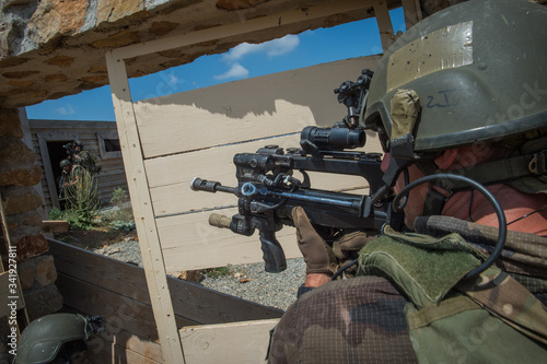 Fotomural a man aiming in the scope of his weapon during a simulation of conflict between