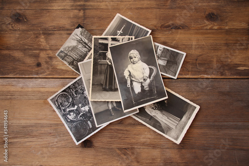 old vintage monochrome photographs in sepia color are scattered on a wooden tabl Canvas-taulu