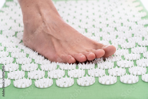 Obraz Female foot on an acupuncture rug. Acupuncture, massage. Alternative medicine. - fototapety do salonu