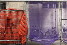 Man With Bicycle Walking On Footpath Seen Through Scaffolding