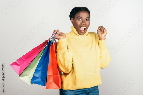 Photo Excited African American woman with shopping bags