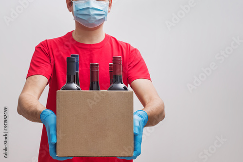 Foto ourier wearing protective mask and gloves holding box with bottles of wine