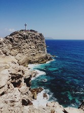 Cross On Cliff Against Blue Sky