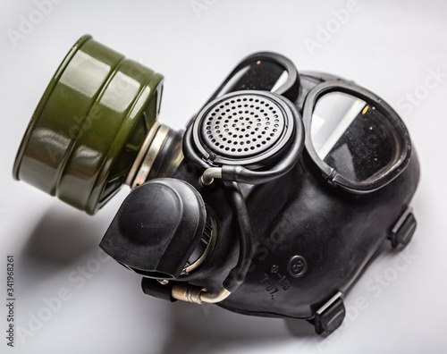 A close up of black commander gas mask with a filter lies on a white background Fotobehang