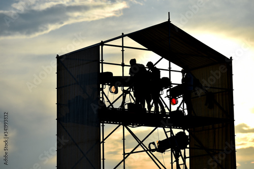 Technical staff and equipment silhouetted against sunset light preparing for a m Fototapet