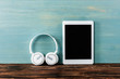 canvas print picture - headphones, digital tablet with blank screen on wooden table near blue wall