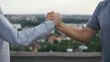 A friendly handshake of two men after meeting outdoors on a sunny day close-up