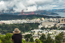 Rear View Of Man By Cityscape And Golden Gate Bridge Against Cloudy Sky