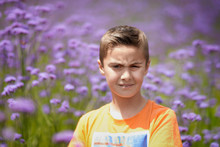 Portrait Of Boy Standing Against Purple Flowers Blooming On Field