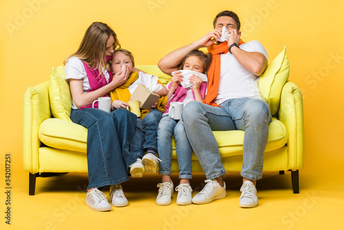 Fotografie, Obraz ill family with kids holding napkins and having runny noses while sitting on sof