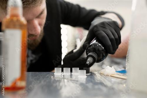 Tattoo master pours black paint Canvas Print