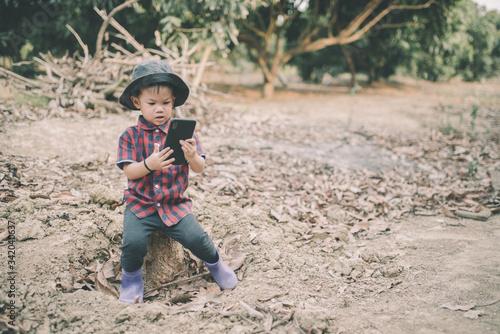 Photo A cute little farmer in Asia wears a red shirt working through a mobile phone
