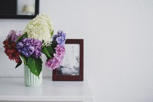 Flower Vase By Picture Frame On Table Against White Wall